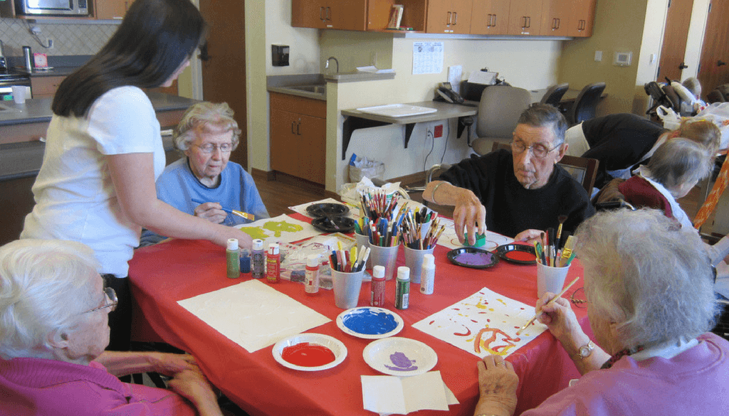 Volunteers helping residents paint at The Neighbors of Dunn County.