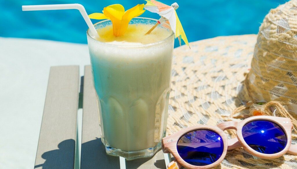 A Piña colada drink next to a straw hat and wooden glasses outside next to a pool.
