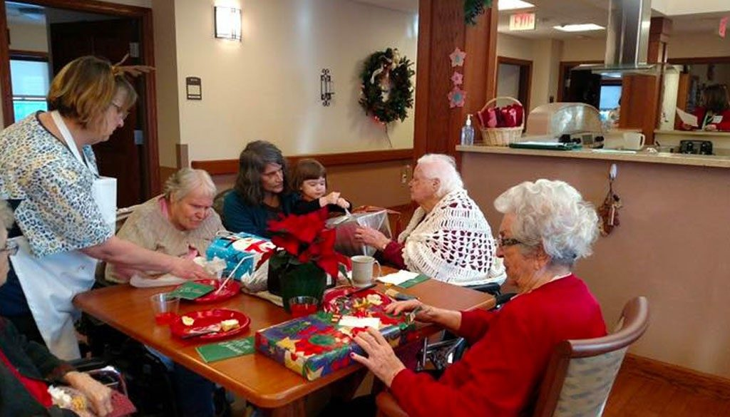 Residents and family opening Christmas presents together at The Neighbors of Dunn County.