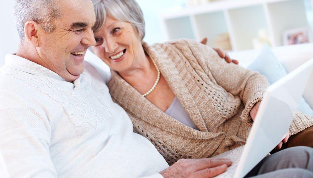 Two laughing seniors using a laptop.