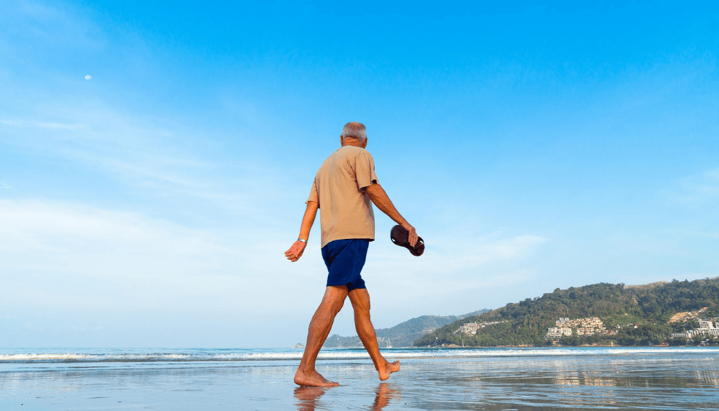 A Senior walking on the beach barefooted