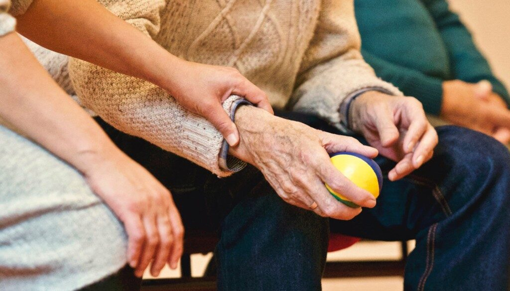 An elderly sqeezing a stress ball with a staff member next to him. Focused on hands.