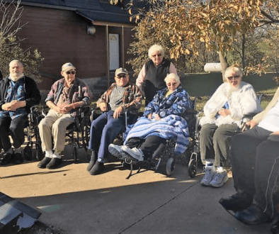 A group of elderly outside sitting in wheelchairs