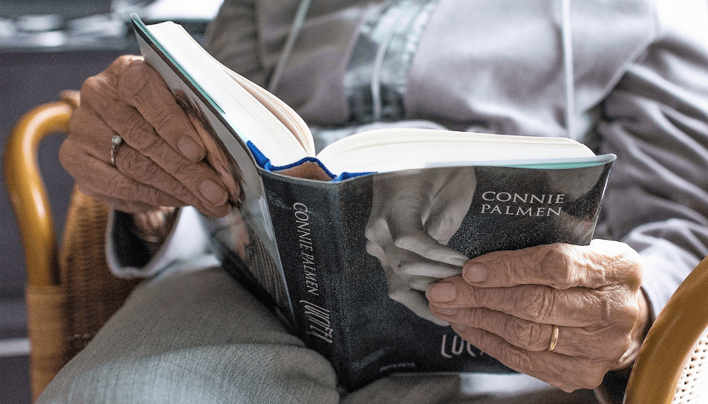 An elderly reading a book, focused on the book and hands.