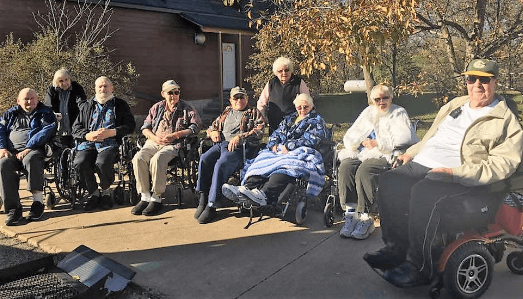 A group of elderly outside sitting in wheelchairs.