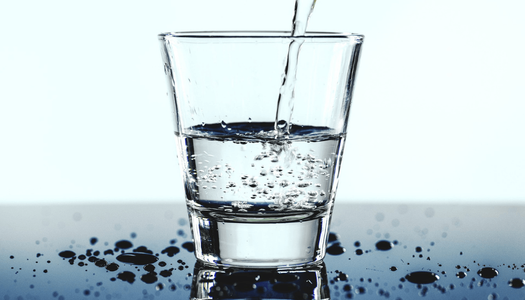 A drinking glass being filled with water.