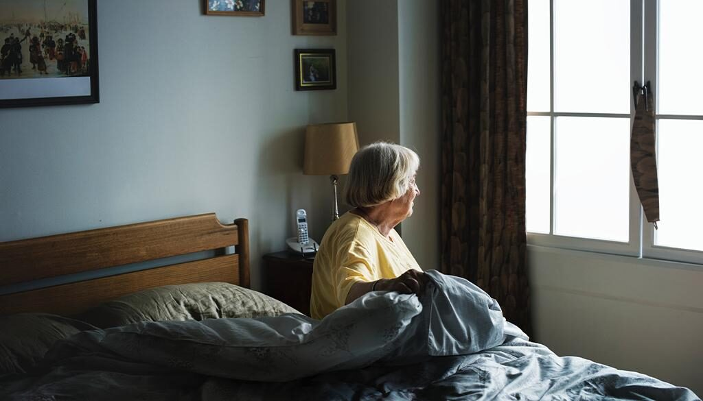 An elderly getting ready to leave the bed while staring out the window
