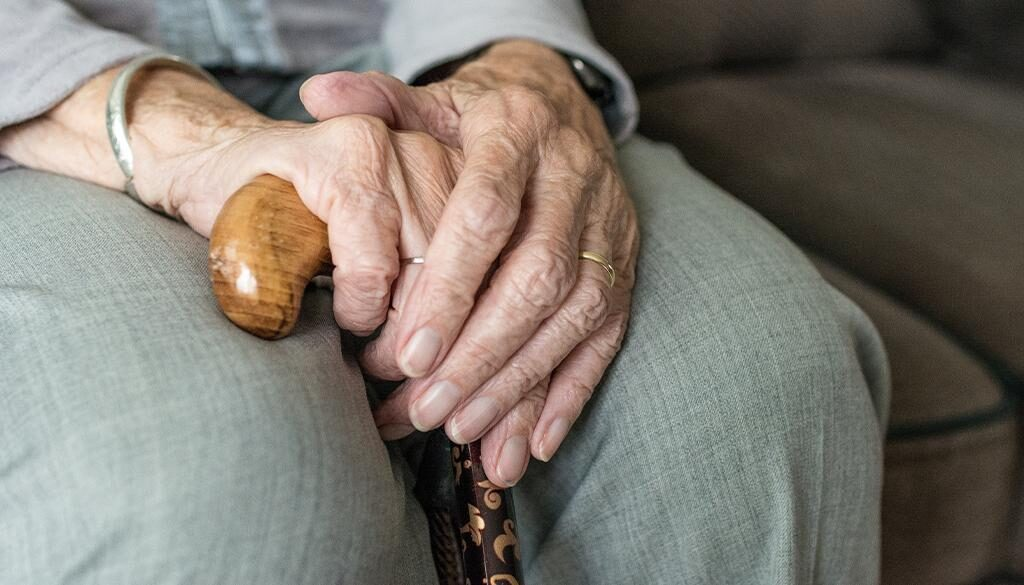 An elderly sitting with their hands on a walking cane