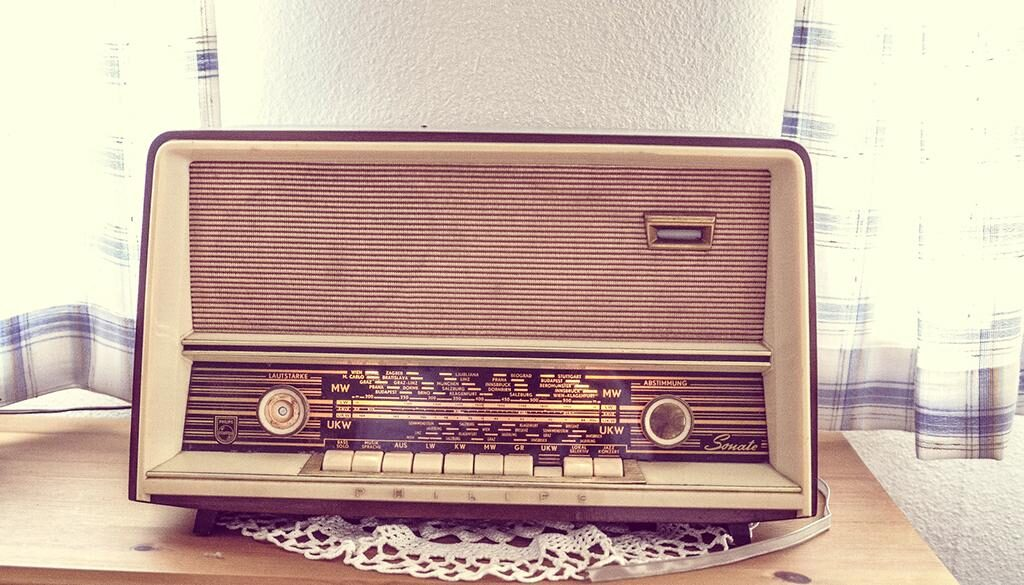 Old radio sitting on a table with a doilie underneath.