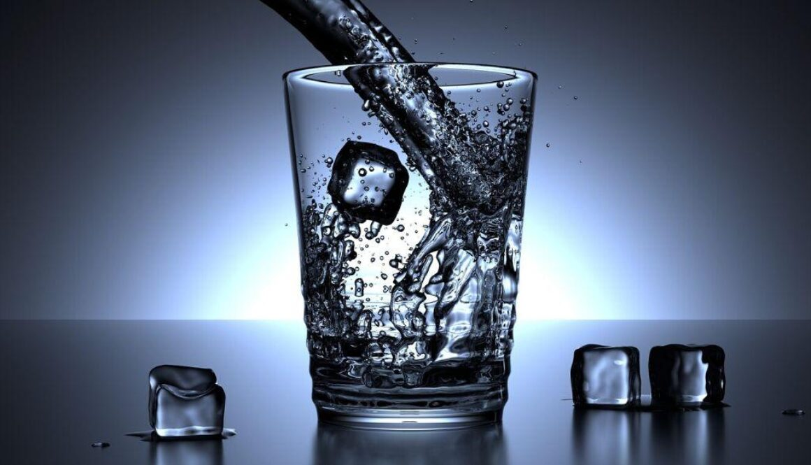 A glass of water being poured with ice cubes.