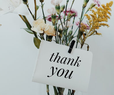 Thank you sign on a vase of flowers.