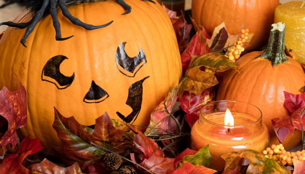 Large Halloween pumpkin with a black jack-o-lantern face painted on it surrounded by fall leaves , smaller pumpkins and a lit candle.