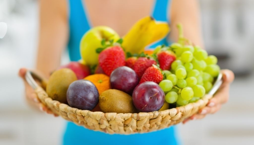 Basket filled with nutrition, grapes, bannanas, apples, plums and strawberrys.